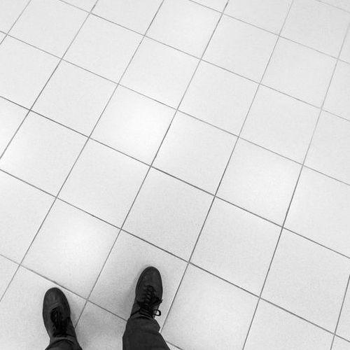 A Man Walks on Tile Office Flooring