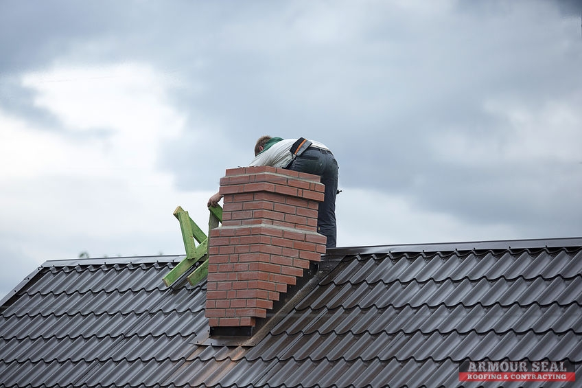 Worker on Roof Behind a Chimney Making Repairs
