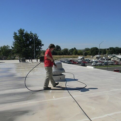 A Contractor Applies a Roof Restoration Coating.