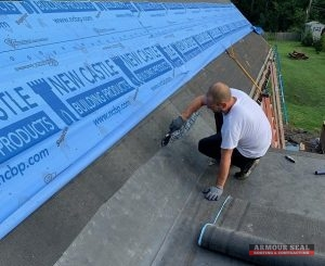Man Applying Tar On Roof So Shingles Can Be Installed