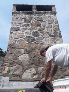 Man Working On Stone Chimney